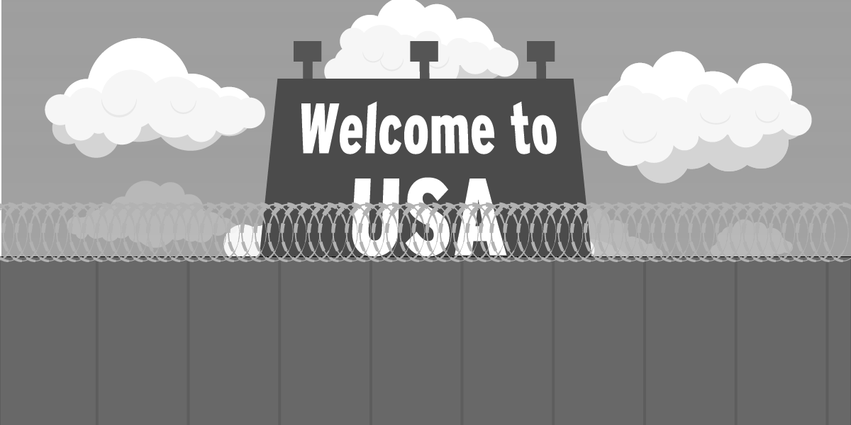 a sign saying welcome to usa positioned behind a wall with barbed wires on top